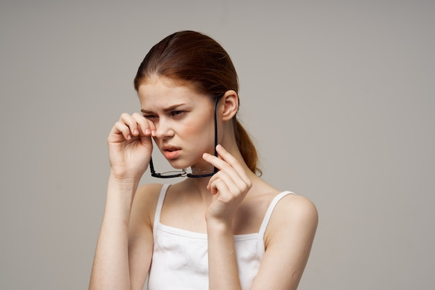 Lunettes de femme mécontente dans les mains de fond clair d'astigmatisme