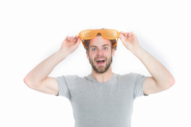 Lunettes de fête orange sur drôle de jeune homme en chemise décontractée isolé sur fond blanc