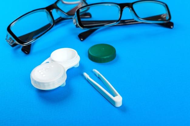 Lunettes, lentilles de contact dans des récipients et pinces à épiler sur fond bleu.