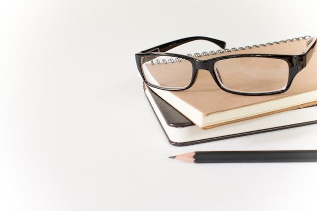 Lunettes, livre et crayon sur blanc