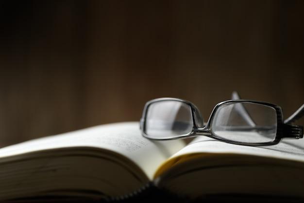 Lunettes sur le livre ouvert, le concept de l'éducation et le ton sombre