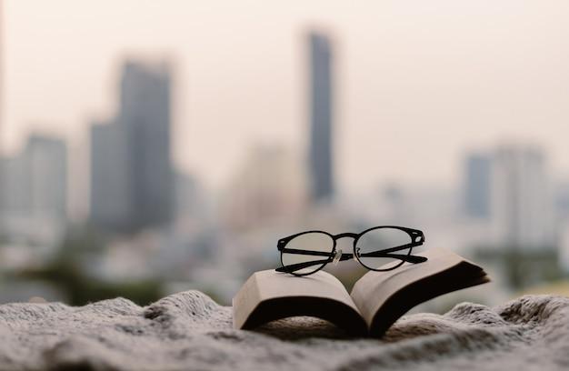 Lunettes sur un livre ouvert sur une couverture avec fond de ville.