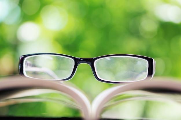 Lunettes sur livre ouvert sur la nature