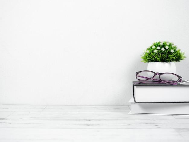 Lunettes sur les livres avec un petit vase sur l'espace de travail du bureau à l'espace de copie à la maison