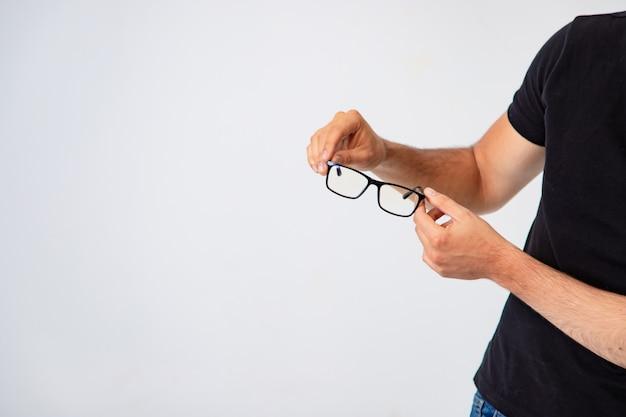Les lunettes à la mode avec un cadre noir sont entre les mains d'un homme