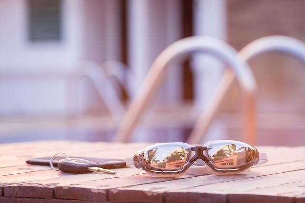 Lunettes de natation sur le bois avec les clés et le smartphone