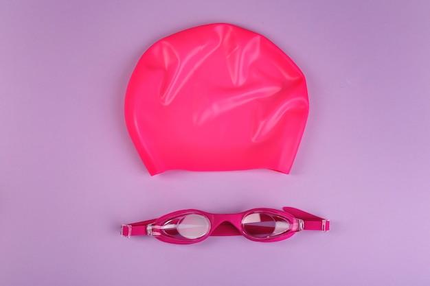 Lunettes de natation et bonnet sur fond violet, mise à plat