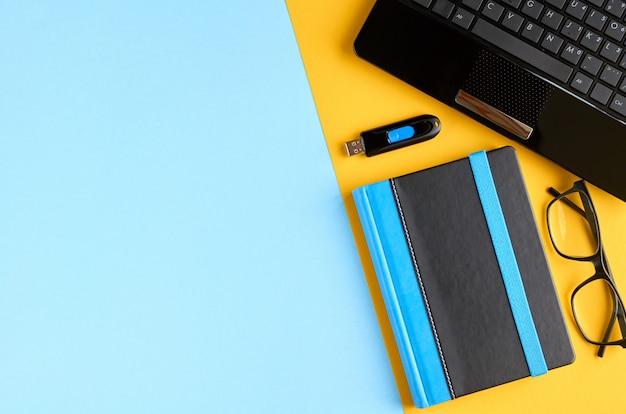 Lunettes noires, cahier, clé usb et clavier d'ordinateur portable sur une surface bleue et jaune.