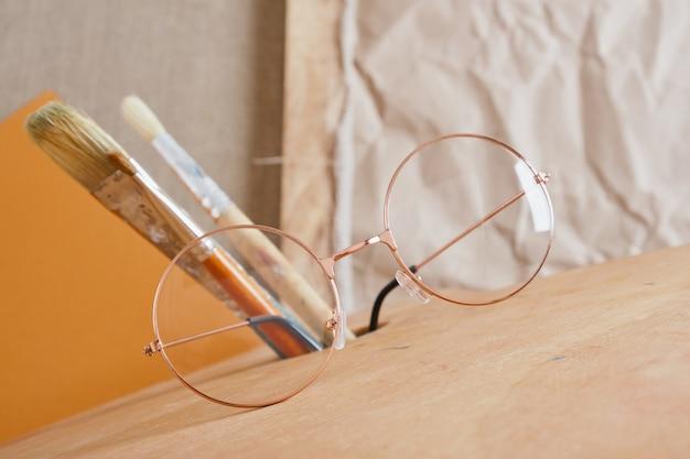 Lunettes sur palette en bois et pinceaux fond marron, concept d'atelier d'artiste