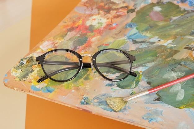 Lunettes sur une palette avec des peintures sur fond marron, concept d'atelier d'artiste