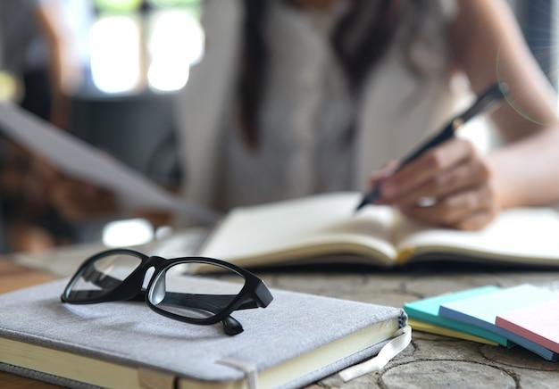 Des lunettes placées sur un cahier, des femmes floues vérifient des graphiques et rédigent des notes.