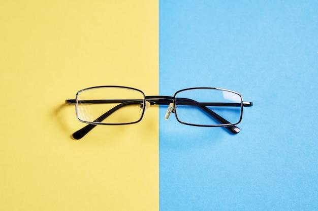 Des lunettes placées sur un fond jaune et bleu pastel divisent les moitiés.