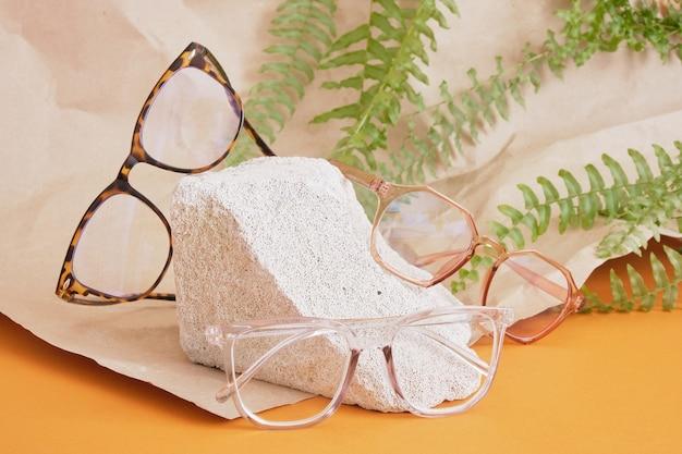 Lunettes sur un podium en béton sur fond marron, composition tendance, lunettes élégantes