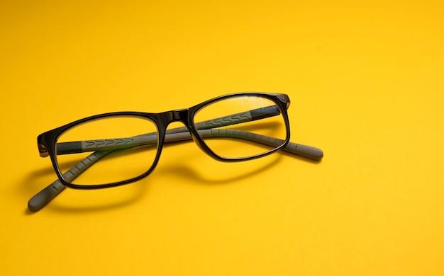 Les lunettes pour enfants reposent sur un gros plan jaune avec un espace pour le texte. copiez l'espace. le concept de myopie des enfants, d'astigmatisme, de problèmes de vision, de déficience visuelle.