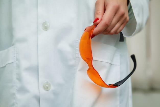 Lunettes de protection orange dans la main du dentiste.