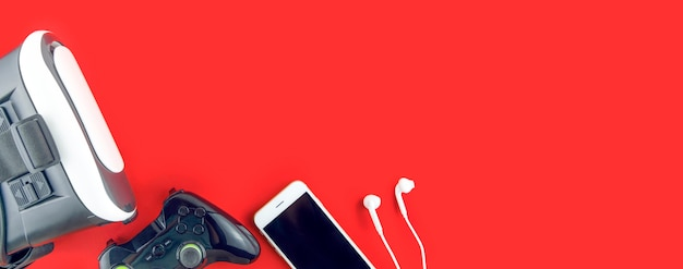 Lunettes de réalité virtuelle 360, manette de jeu et téléphone sur une table rouge