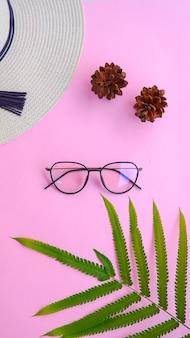 Lunettes rondes sur la photo dans un style estival minimal sur fond de couleur rose pastel.