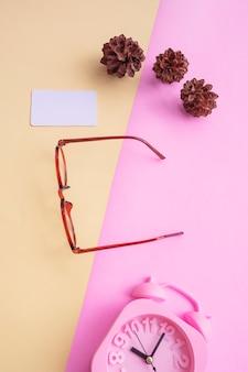 Lunettes rondes sur la photo dans un style estival minimal sur fond rose et jaune pastel. réveil , fleurs de pin , cartes de visite