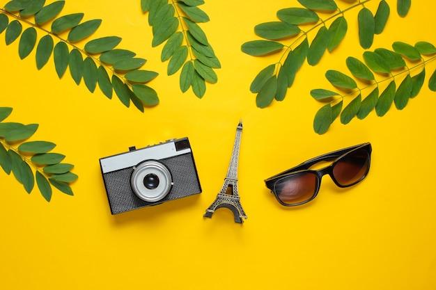 Lunettes de soleil, appareil photo rétro, figurine de la tour eiffel sur fond jaune avec des feuilles vertes. contexte de voyage.