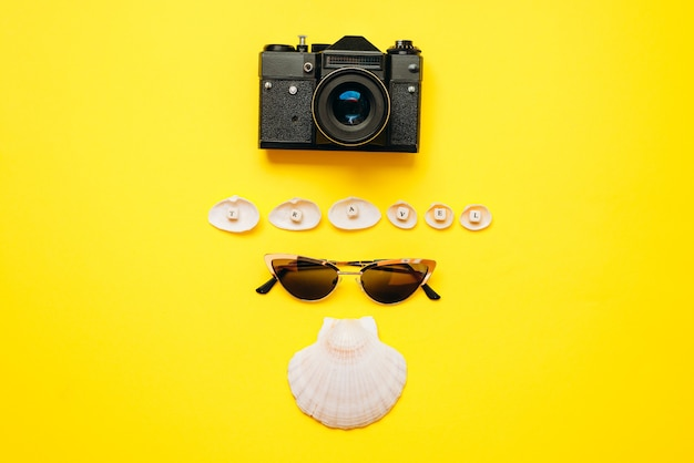Des lunettes de soleil, un appareil photo vintage et des coquillages sont disposés