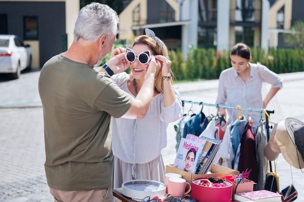 Lunettes de soleil blanches. drôle de femme aux cheveux blonds essayant de grandes lunettes de soleil blanches en venant à la vente de garage avec son mari barbu