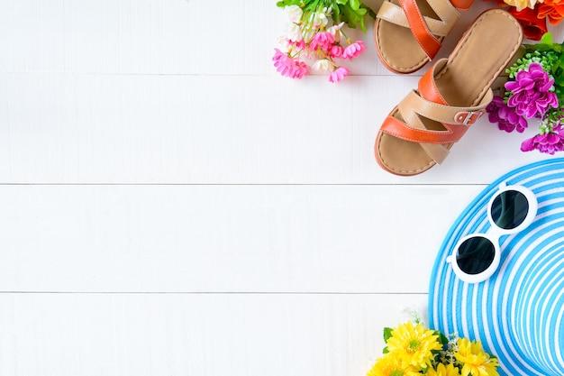 Lunettes de soleil chapeau bleu et chaussure sur une table en bois blanc