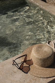 Lunettes de soleil et chapeau de paille sur le côté de la piscine en marbre avec de l'eau bleu clair avec des reflets d'ombre du soleil des vagues