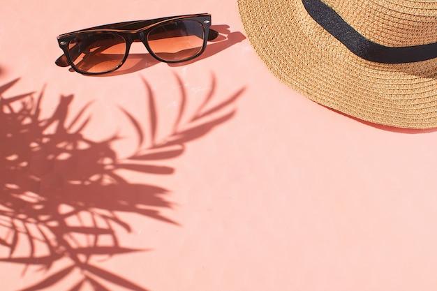 Lunettes de soleil chapeau de paille fond rose vue de dessus espace de copie