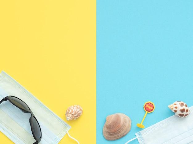 Lunettes de soleil, coquilles et panneau routier d'arrêt se trouvent sur des masques médicaux sur double bleu et jaune