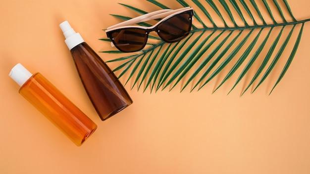Lunettes de soleil, crème solaire et feuilles de palmier. mise à plat, vue de dessus sur fond orange doux