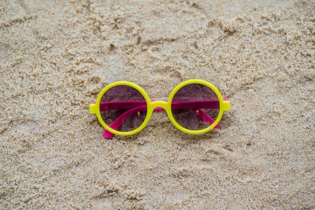 Lunettes de soleil dans le sable à la plage
