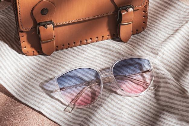 Des lunettes de soleil dégradées à monture transparente et un sac en cuir marron sont sur un tissu de coton à rayures grises