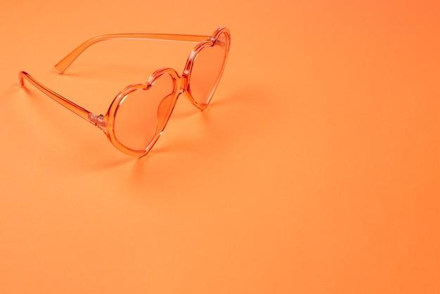 Des lunettes de soleil d'été reposaient sur des cheveux roses sur un mur orange. copiez l'espace.