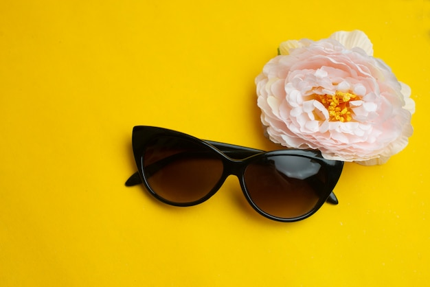 Lunettes de soleil femme avec fleur sur la surface jaune.