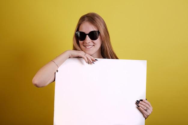 Lunettes de soleil fille de gingembre se cache pour la peinture blanche sur fond jaune