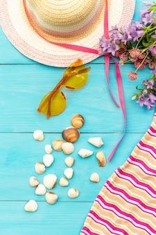 Lunettes de soleil, fleurs, coquillages et chapeau de paille
