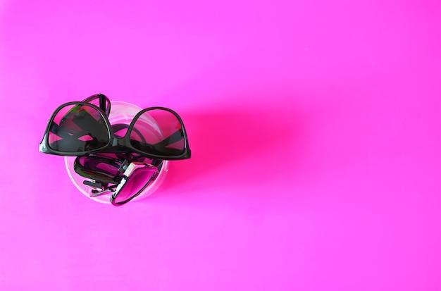 Lunettes de soleil sur fond pastel rose. lunettes avec montures noires. accessoires de mode de protection uv des yeux.