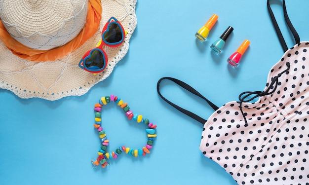 Lunettes de soleil en forme de coeur, chapeau de paille, une robe et plus d'accessoires d'été sur fond bleu