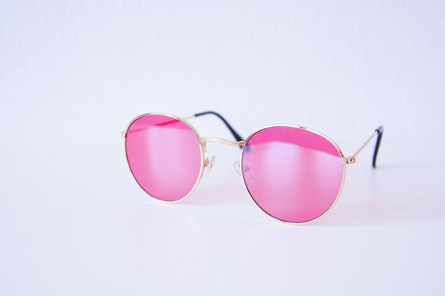 Lunettes de soleil fraîches de lumière rose moderne isolés. concept de vacances de voyages d'été. kit de vente. protection des yeux. mise au point sélective