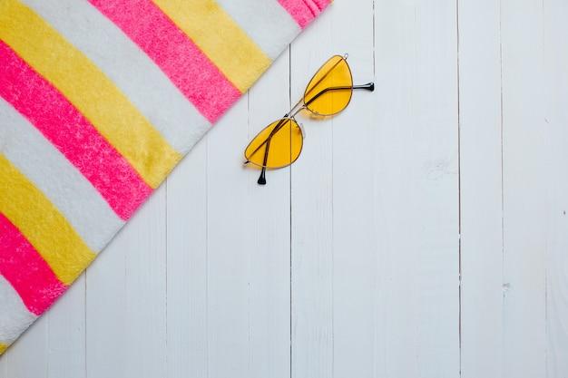 Lunettes de soleil jaunes et serviette colorée à rayures sur le bois blanc