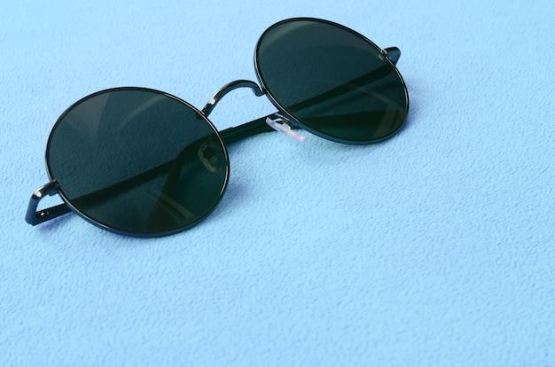 Des lunettes de soleil noires élégantes avec des lunettes rondes reposent sur une couverture en polaire doux et moelleux bleu clair.