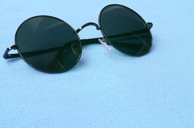 Lunettes de soleil noires élégantes avec des lunettes rondes se trouve sur une couverture en doux