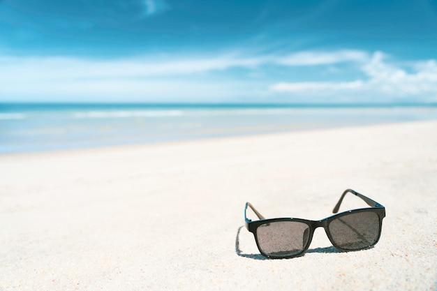 Lunettes de soleil sur la plage de sable blanc avec une mer de couleur turquoise en été journée ensoleillée