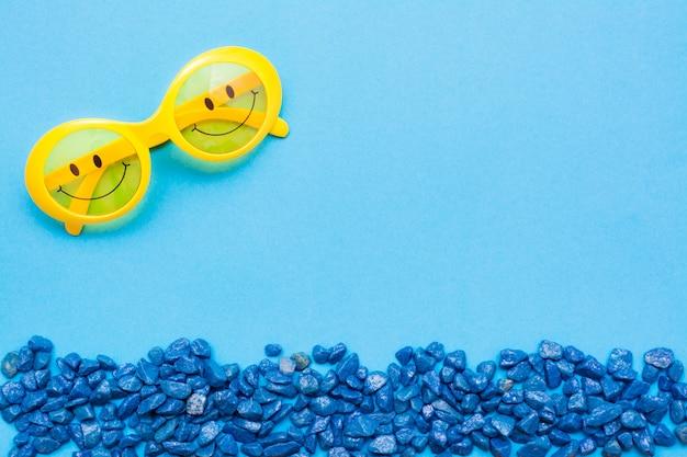 Lunettes de soleil en plastique jaunes avec des yeux peints et un sourire sur les lunettes et des pierres bleues décoratives sous la forme d'une vague de la mer sur un fond bleu