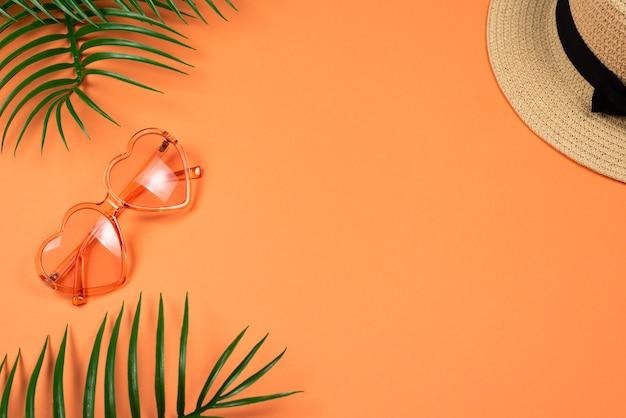 Lunettes de soleil roses et un chapeau sur fond orange