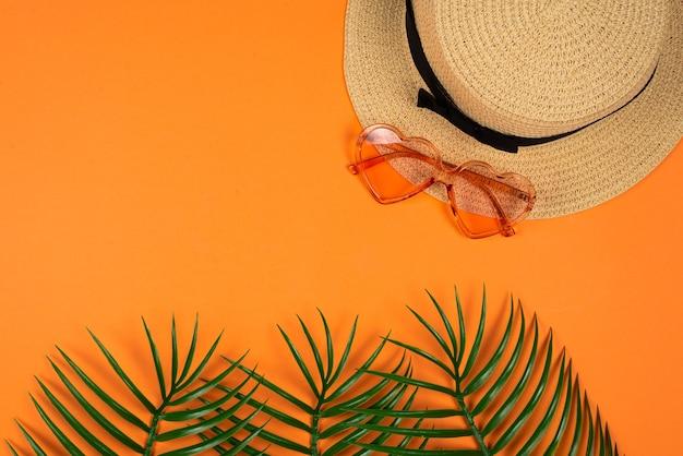 Lunettes de soleil roses et un chapeau sur un mur orange. copiez l'espace.