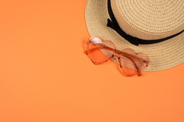 Lunettes de soleil roses et un chapeau sur l'orange