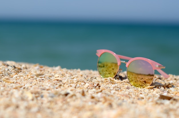 Lunettes de soleil roses contre le soleil sur le sable de la plage