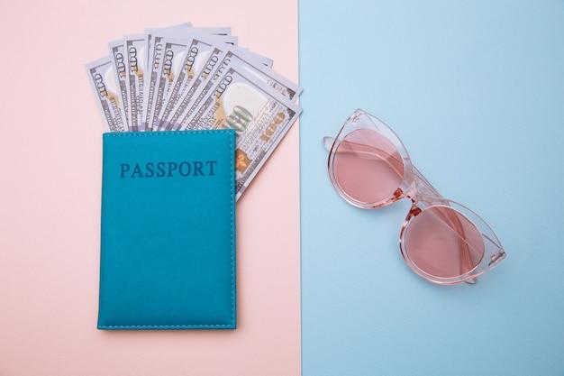 Lunettes de soleil roses et passeport avec de l'argent