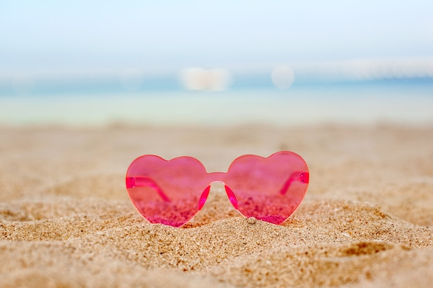 Lunettes de soleil roses sur une plage de sable avec un fond de mer bleue, lune de miel, vacances, espace copie